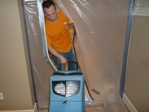 Water Damage Green Technician Using Air Mover Near Vapor Barrier